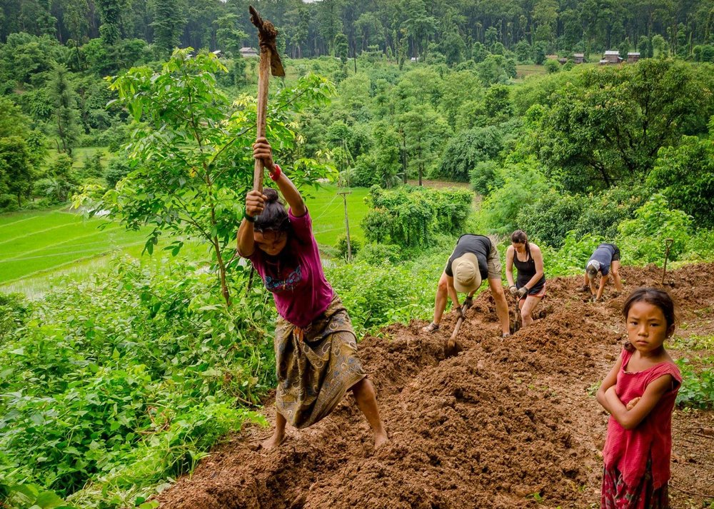 Local women and volunteers dig paths for pipelines in Nepal.