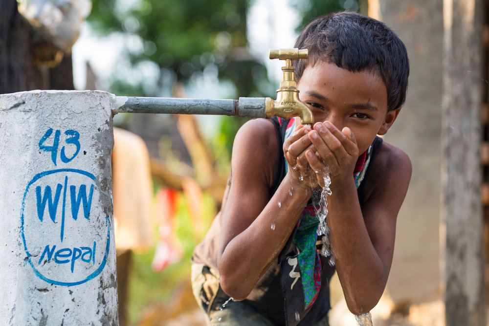 A young boy from the Raitole community enjoys a refreshing drink of clean water from tap stand #43. There are over 70 tap stands throughout the village, each placed right outside each family's door.