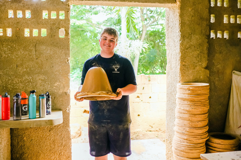 Neo Sanders showing off a ceramic water filter he made in the Dominican Republic