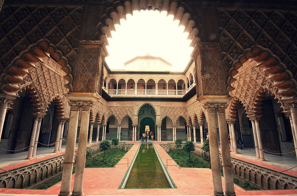 The Courtyard of the Maidens at the Alcázar of Seville  By Cat from Sevilla, Spain - Patio de las Doncellas, CC BY 2.0