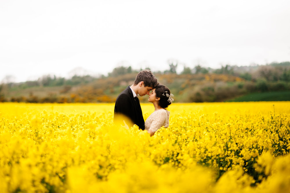 A husband and wife hold each other amongst a field of yellow rapeseed