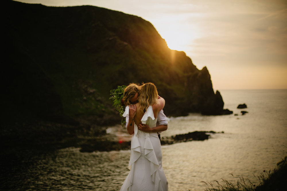 A husband and wife hold each other against a back drop of the setting sun over a cliff