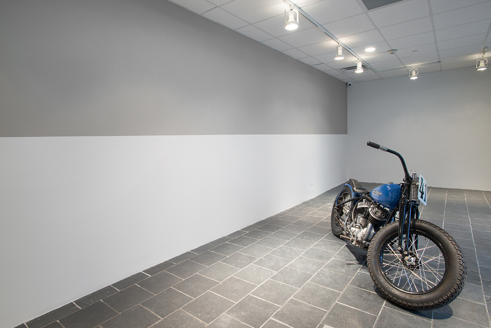 Installation view:  Olivier Mosset , Hunter College Art Galleries, 2016. Photo by Bill Orcutt. Left to right:  Untitled , 1999-2016. Latex paint on wall, dimensions variable. Courtesy of the artist and Christopher Grimes Gallery, Santa Monica.  Da 1962 . 1962 Harley Davidson, 45 cubic in., 750 cubic cm. Courtesy of the artist and Martos Gallery, New York.
