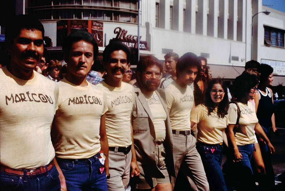Participants in the Christopher Street West Pride parade wearing Joey Terrill's  malflora  and  maricón  T-shirts, June 1976. Terrill appears third from the left. Photo by Teddy Sandoval. Courtesy of Paul Polubinskas.