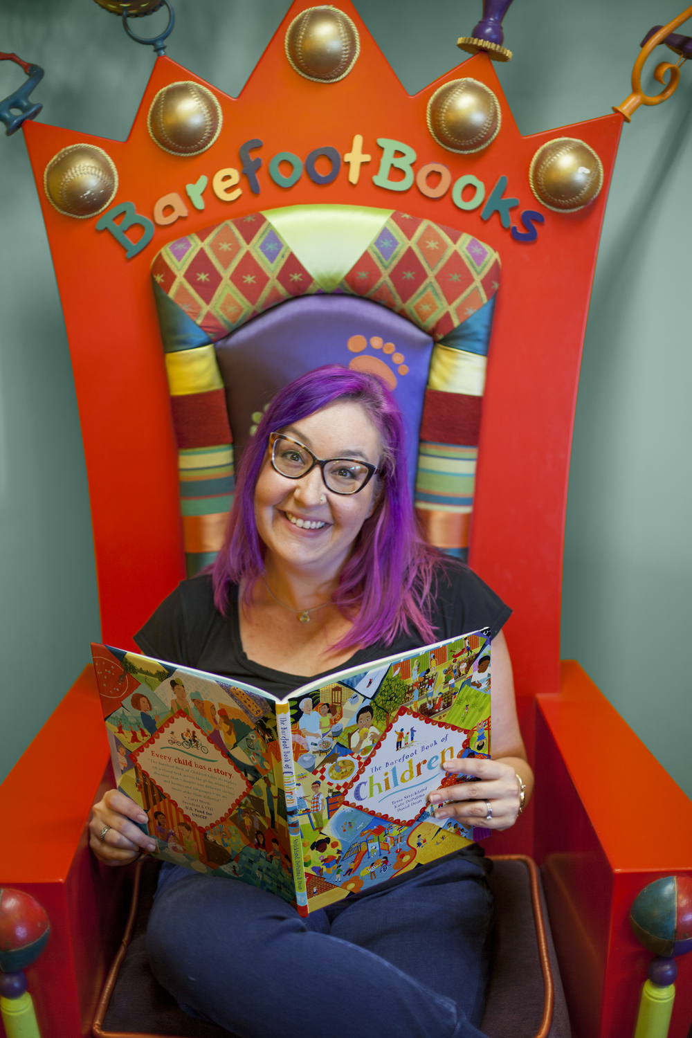 Kate DePalma on the famous Barefoot Books throne with  The Barefoot Book of Children.  Photo by Sarah Soldano.