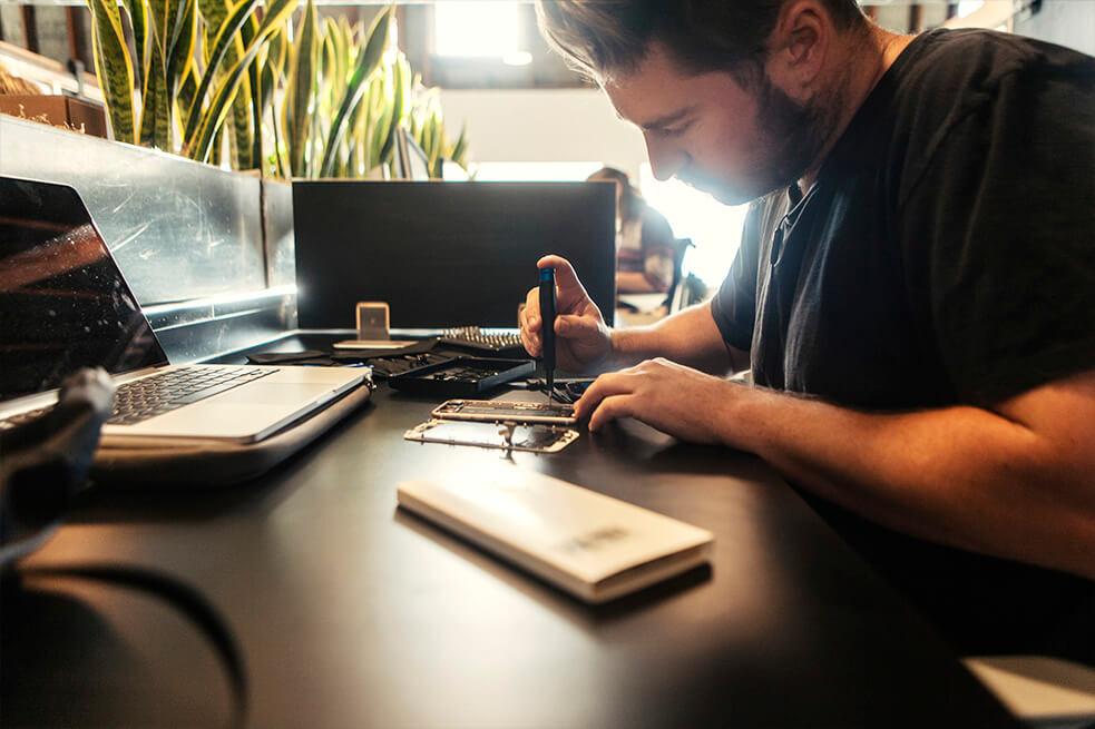 Travis Thomas fixing an iphone at the impact hub in state street santa barbara 03.jpg