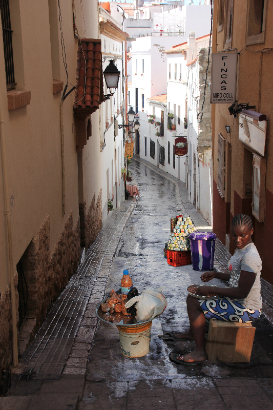A Trader From Marina, Lagos Selling Her Wares In A Side Street In Sitges, Spain.