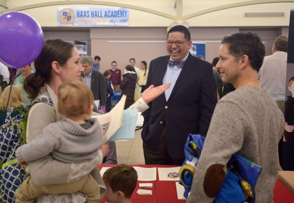 BEN GOFF • @NWABENGOFF Credit: NWA Democrat-Gazette  John Rocha, Ozark Catholic Academy head, talks to Mundo Harbaugh (right) and wife Jennifer Harbaugh with sons Henry Harbaugh, 4, and Leo Harbaugh, 15 months, of Rogers on Saturday during the Northwest Arkansas School Choice festival at the Jones Center in Springdale. The academy plans to open in the fall of 2018 in the Springdale or Tontitown area. The event, held as part of National School Choice Week, was an opportunity for families to learn about Northwest Arkansas private, public and charter schools, home-school groups and other education resources.