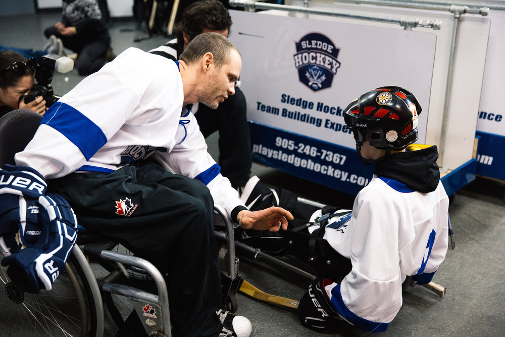 Here, Kris Dutkiewicz, the lead role next to Kevin Rempel at the Sledge Hockey Experience helps Alex Luey, a cancer survivor get into his sled at the Niagara Sport Commission's community based event