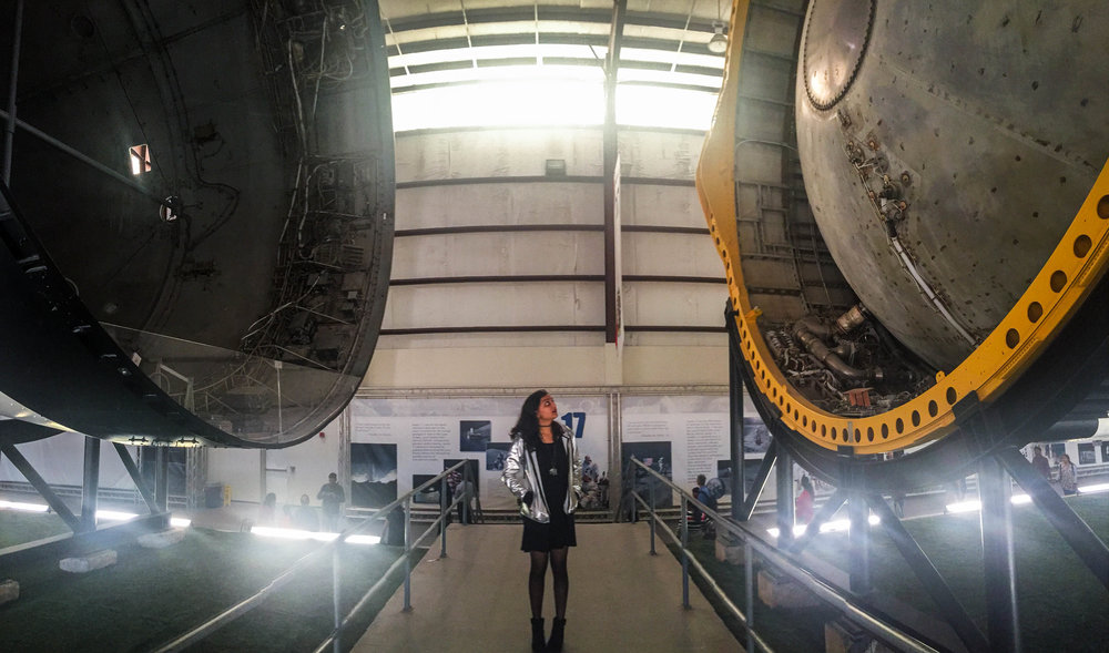 Me between parts of the Saturn V Rocket which was used in the 1960's and 70's to launch people to the moon.