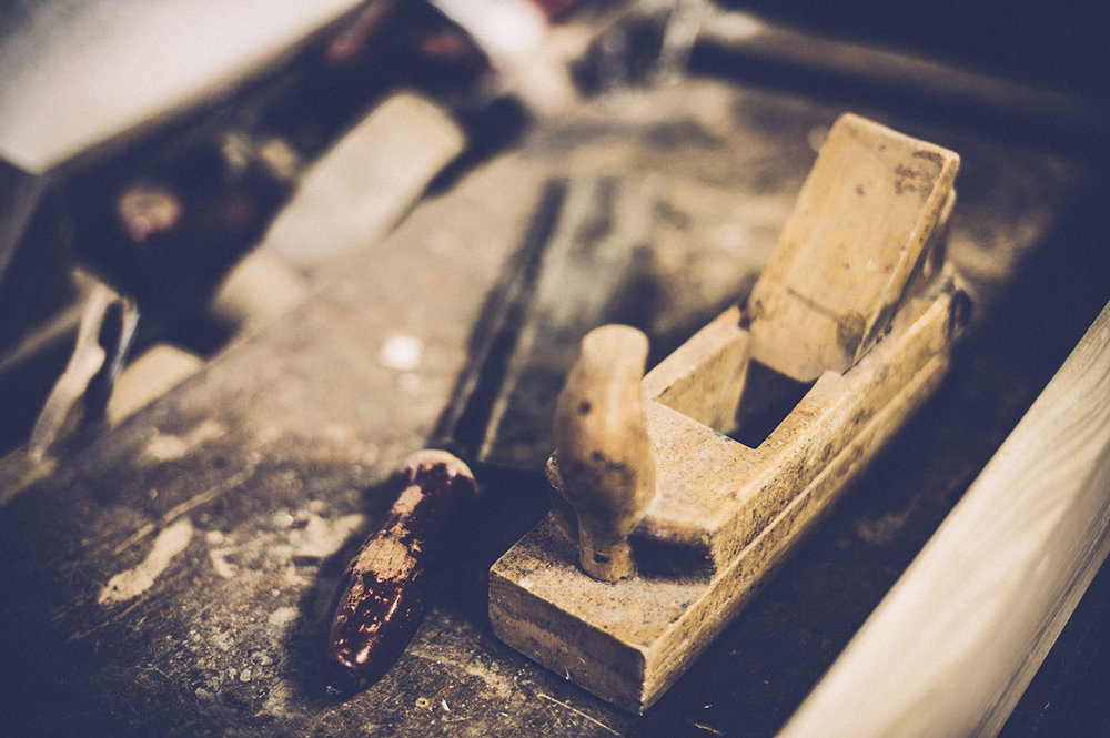 stock-photo-86600605-hand-smoothing-plane-on-a-workbench.jpg