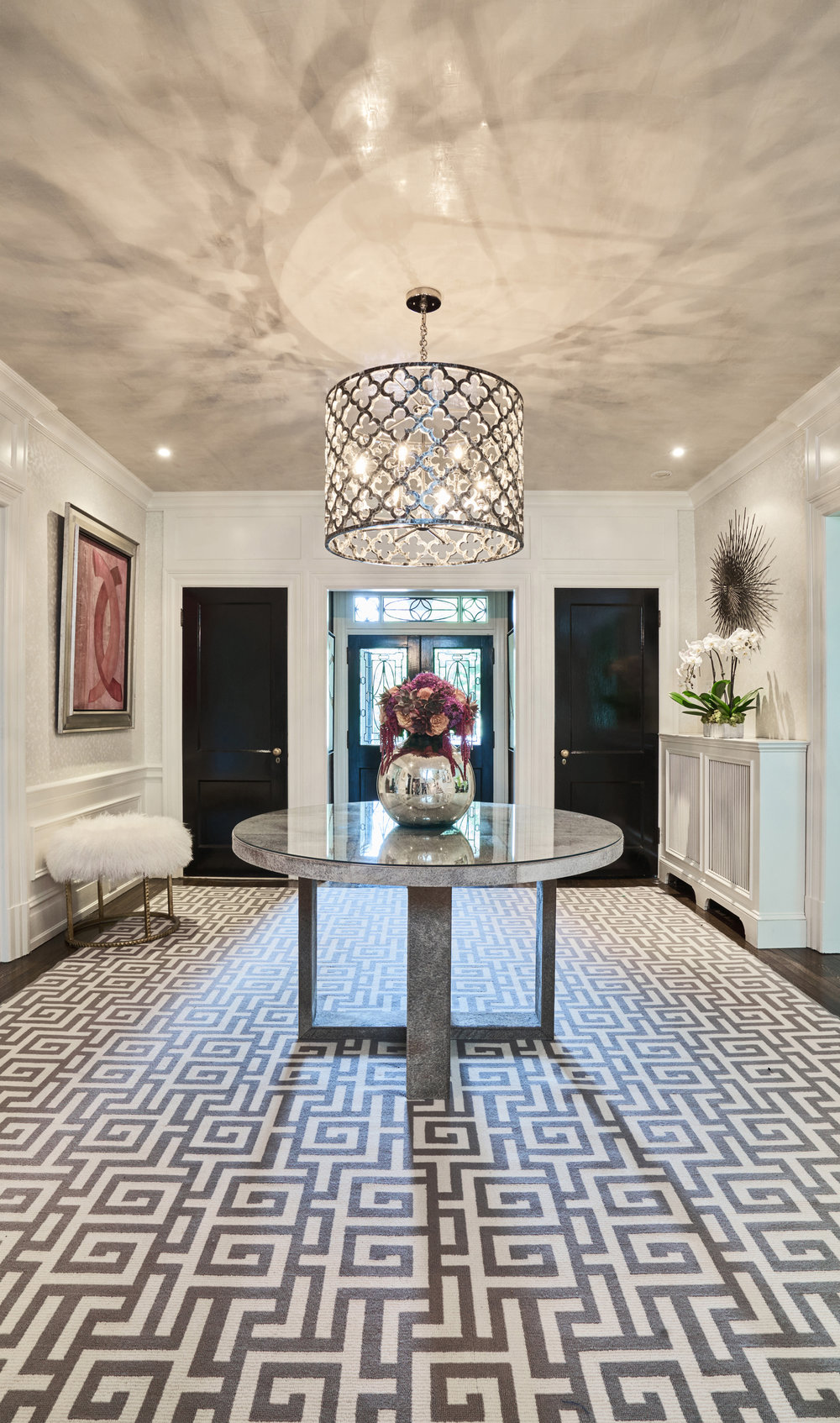 Graphic rug gives foyer a modern take against a traditional background.