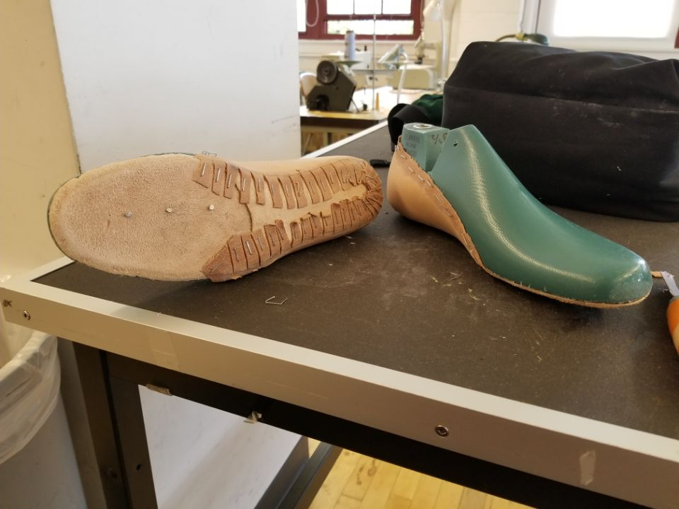 Leather sole and heal counter are soaked in warm water, and stretched over the shoe last.