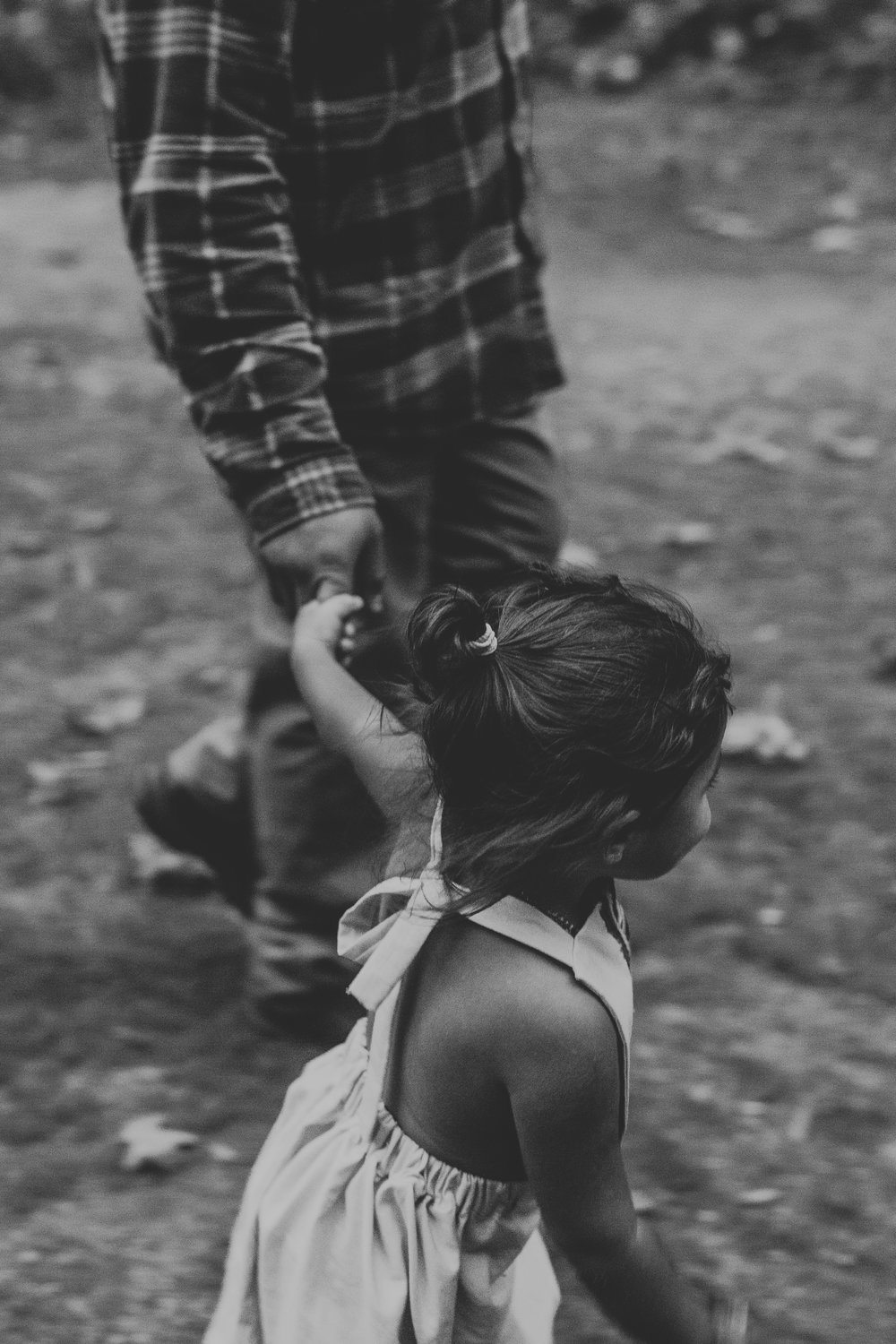 Toddler girl pulling father by hand.