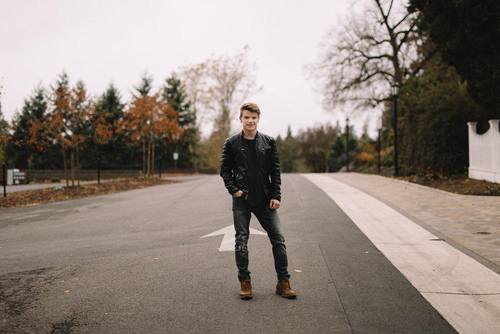 Senior standing in road at Jacksonville Oregon.