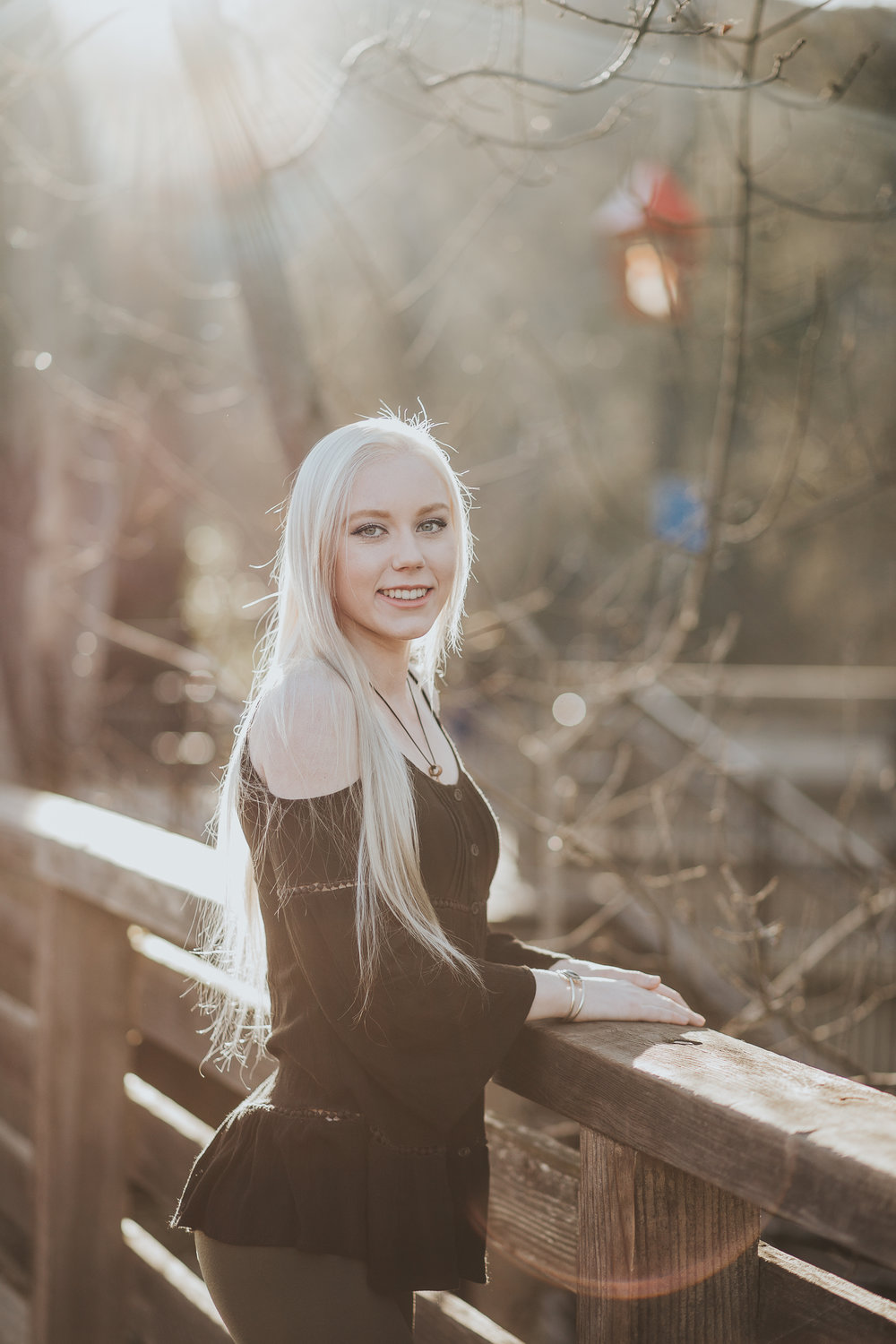 Senior girl leaning on railing sun shining in hair