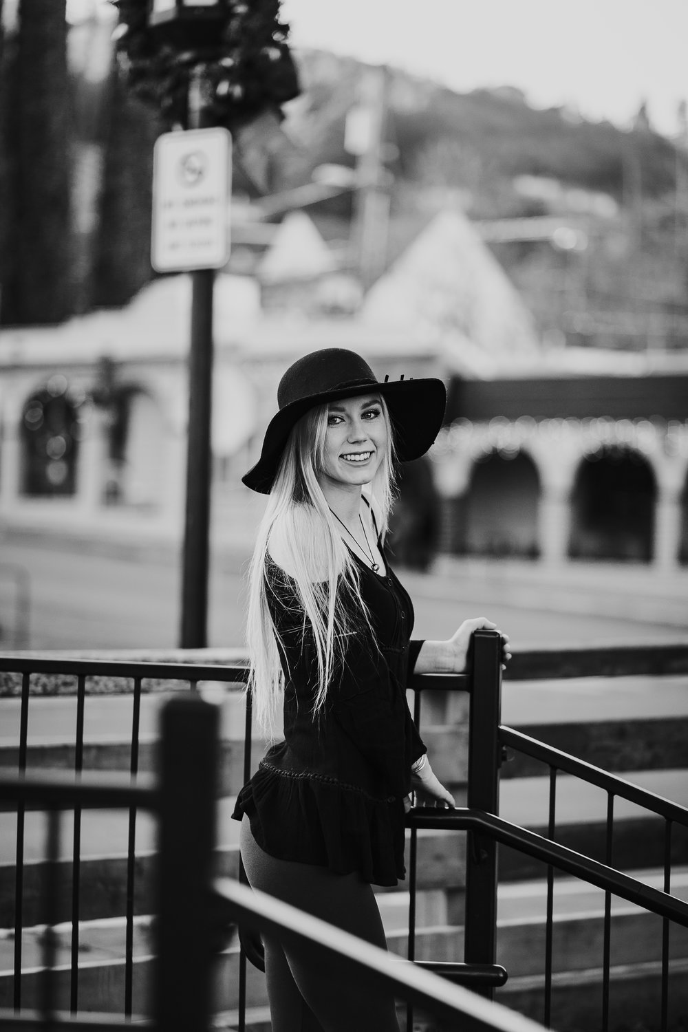 Senior girl in hat leaning on railing downtown