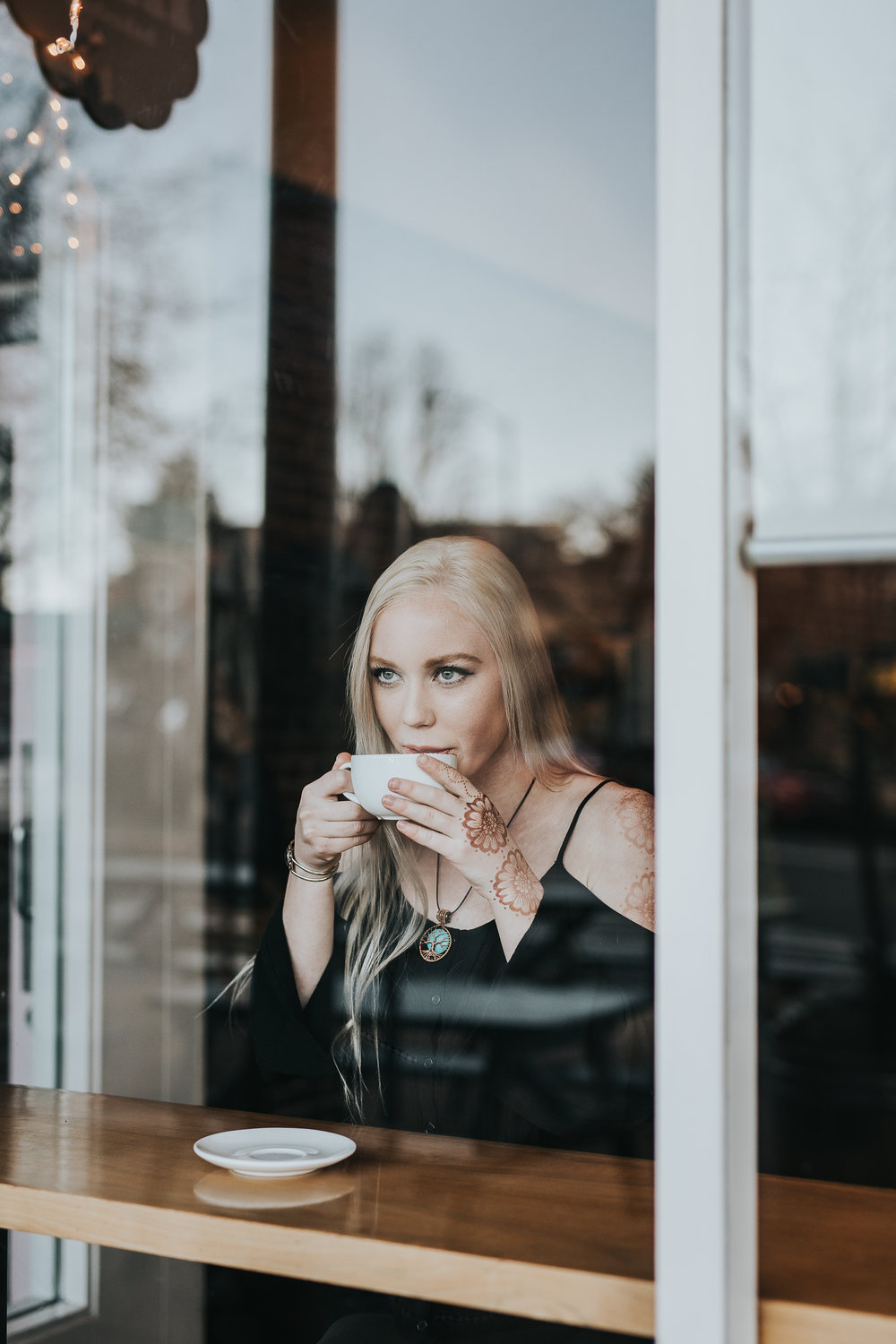 Senior drinking coffee through window of coffee shop