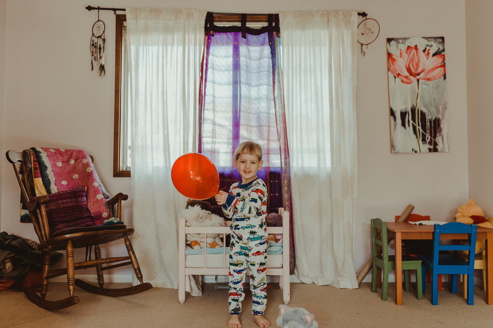 Toddler boy wearing pajamas playing with red balloon in Southern Oregon home.