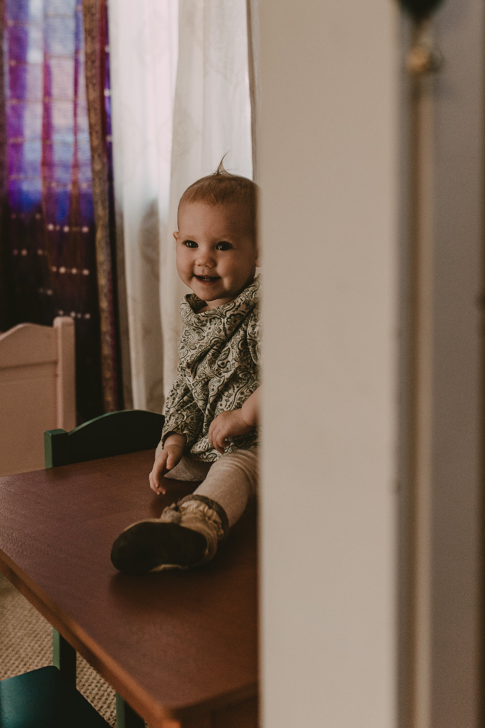 Toddler girl sitting on table peeking around corner giggling