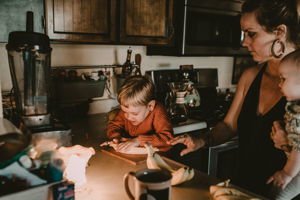 Toddler boy cutting banana with Mom