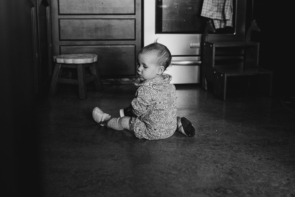 Little girl sitting on kitchen floor