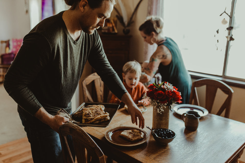 Dad serving breakfast to family at table