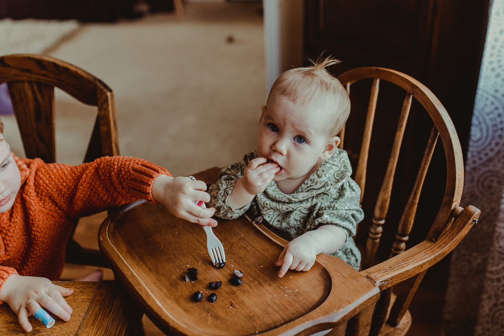 Baby in highchair eating blueberries brother helping