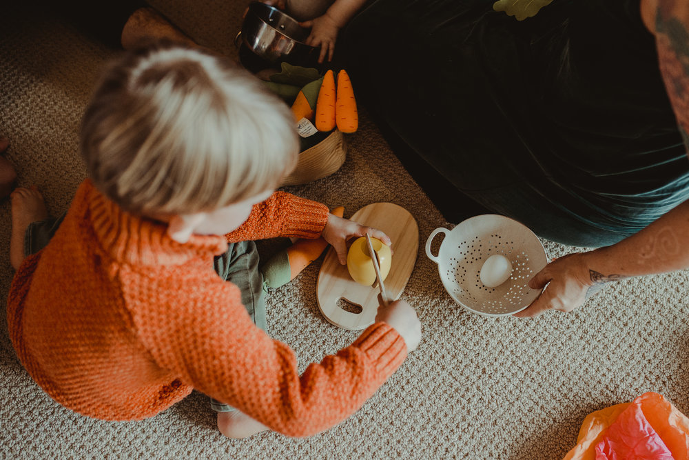 Toddler playing with wooden food