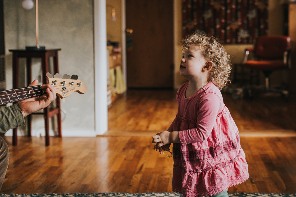 Toddler captivated by Dad playing guitar.