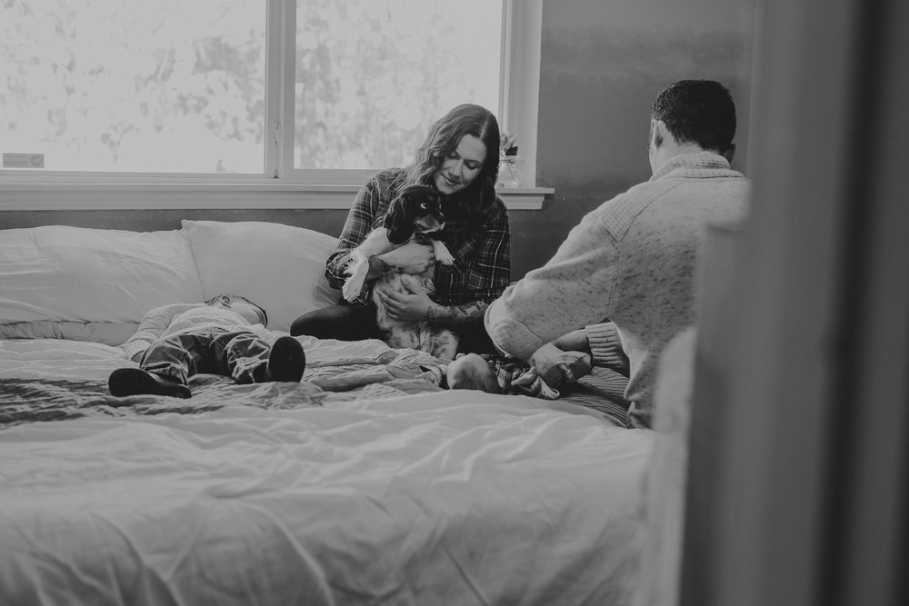 Family dressing newborn and playing with dog on bed.