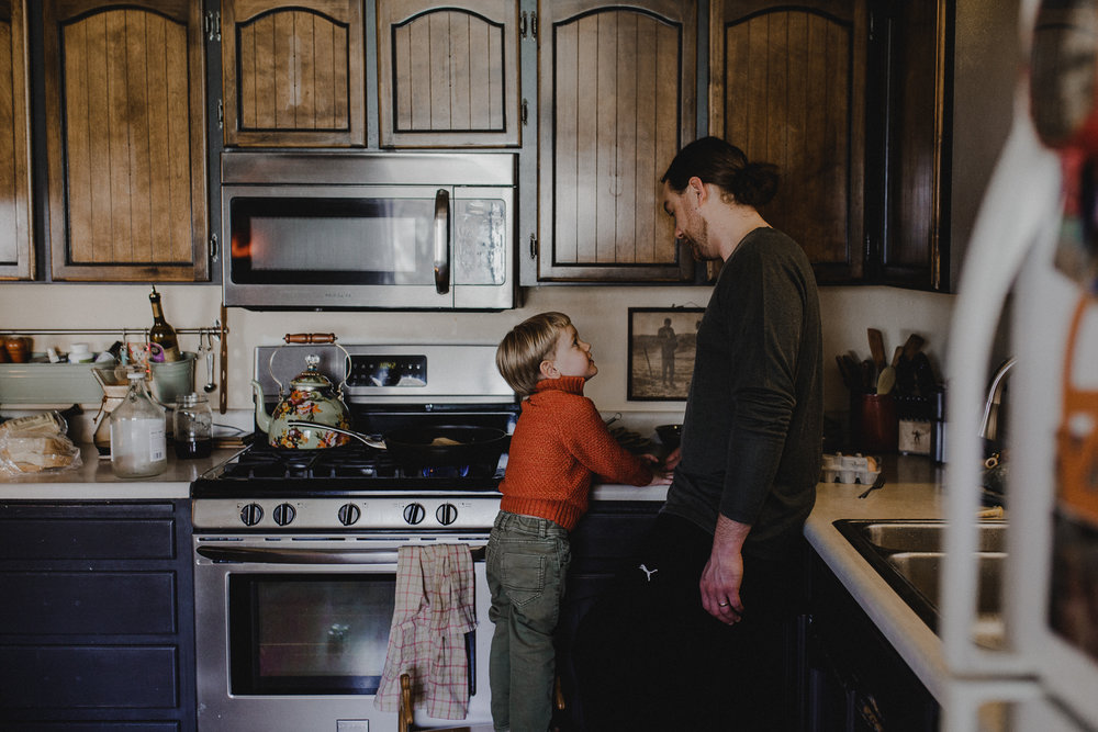 Boy looking up at dad in kitchen of their Talent Oregon home