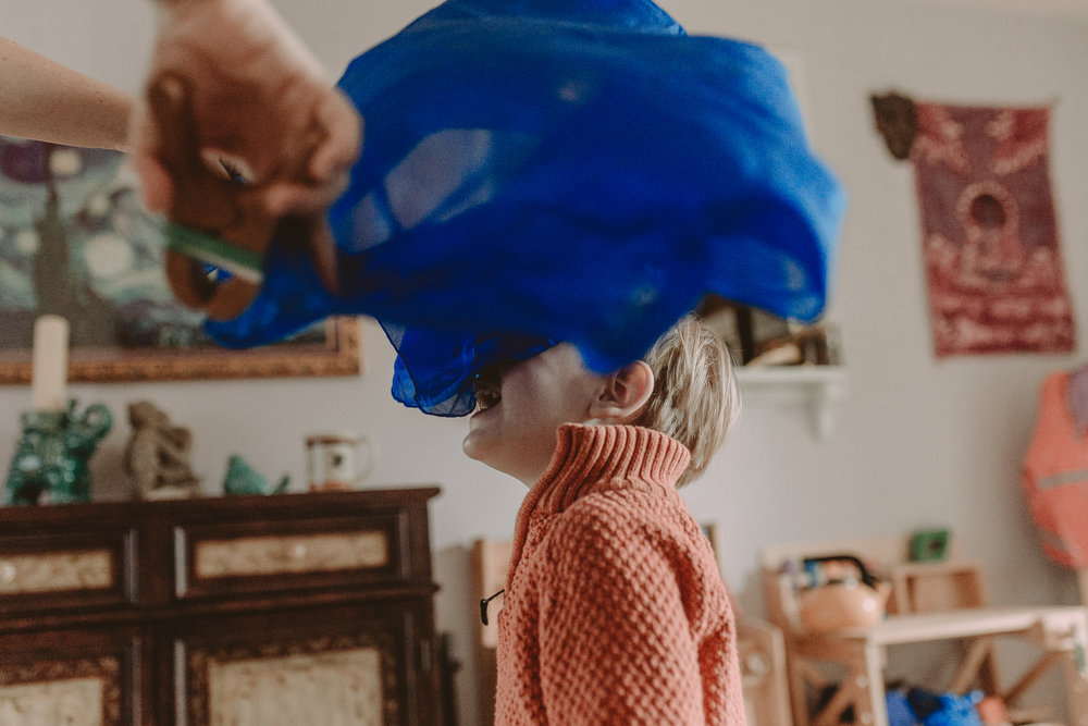 Dad tossing silks over toddler's head