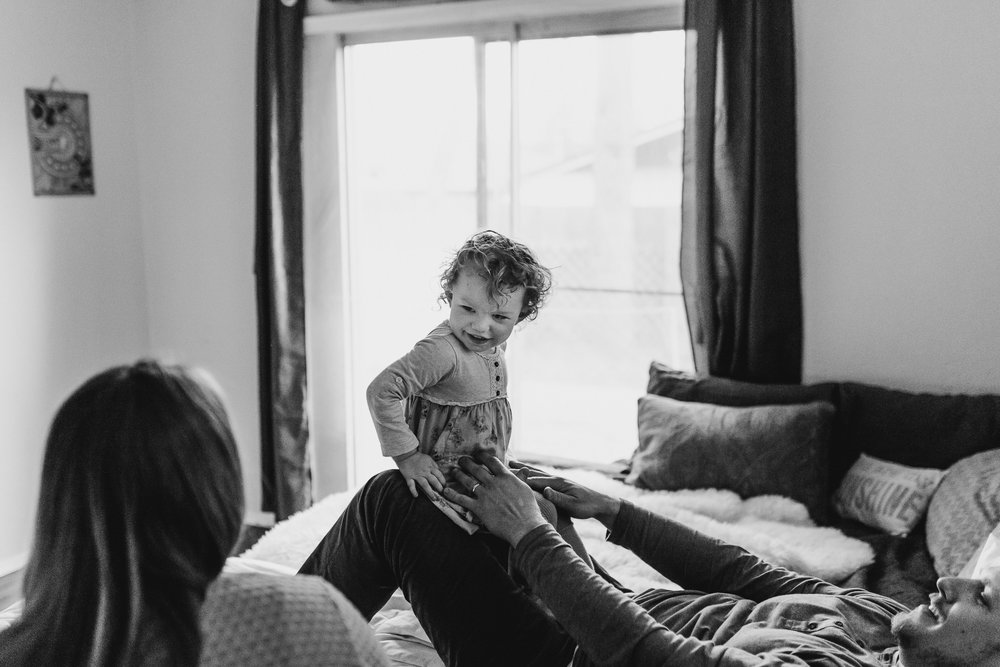 Toddler laughing on daddy's knees looking at mom