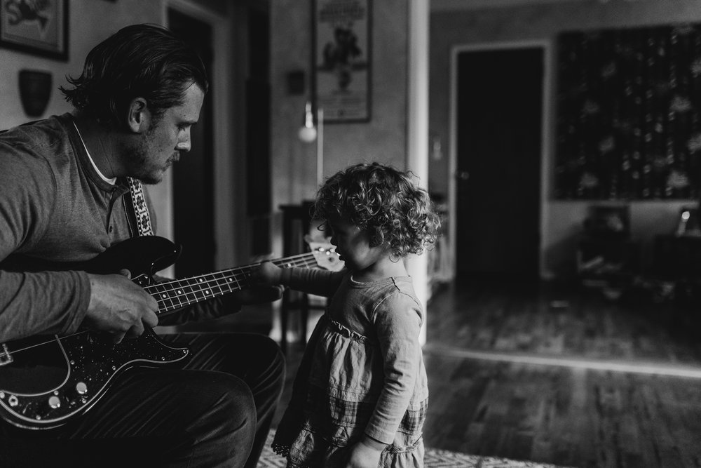 Dad playing guitar with toddler