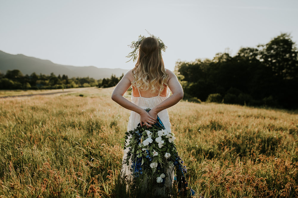 Oregon Bride holding wild bouquet behind back