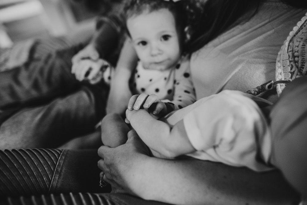 toddler girl holding newborn's hand