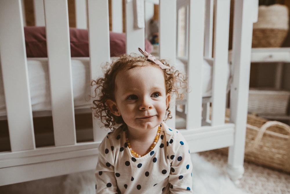 toddler girl smiling in front of crib