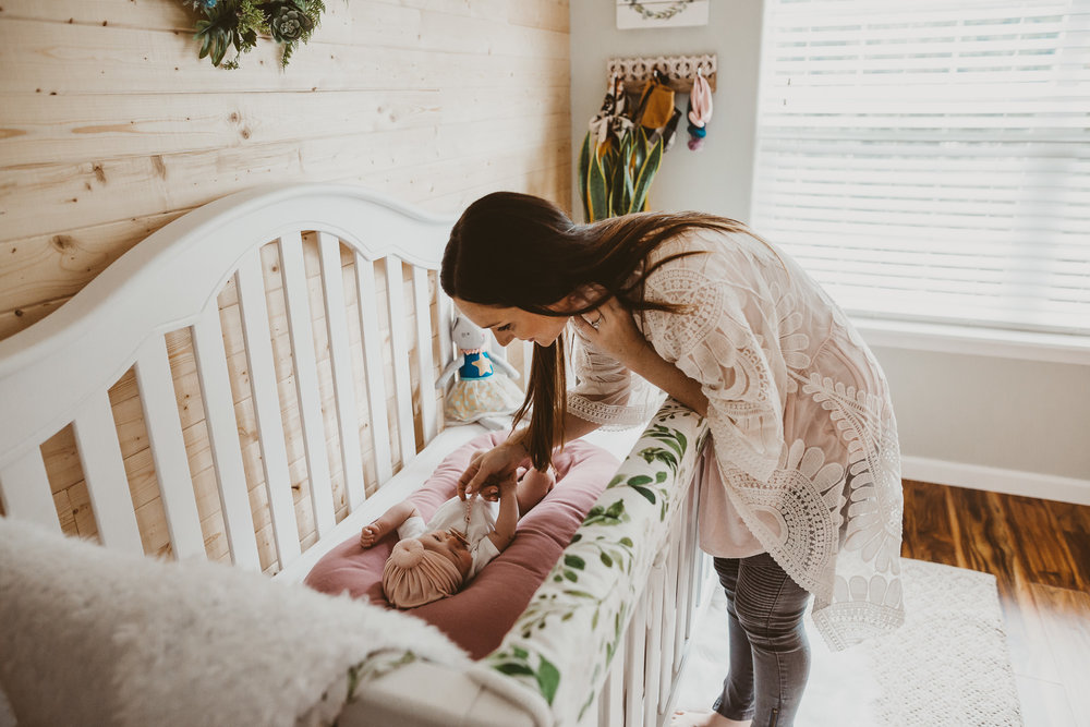 mother looking over newborn girl in medford Oregon home