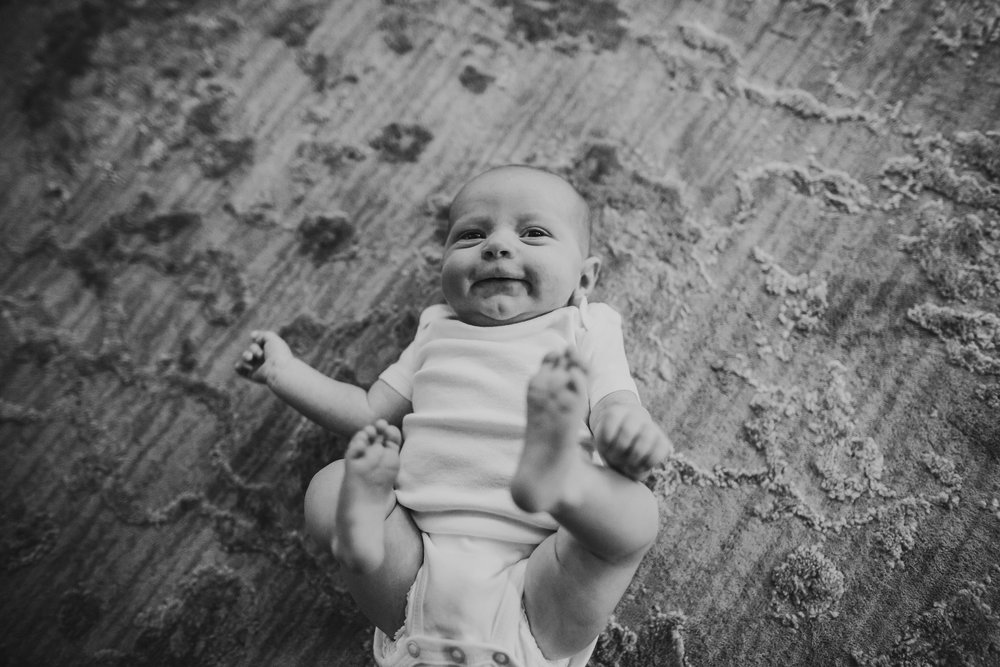 baby holding toes smiling