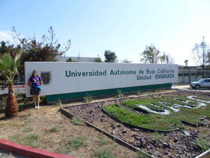 Caption: Lydia standing by the sign of the host university where her club was held.