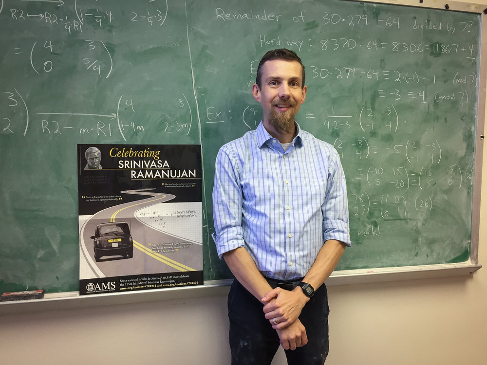 Karl Mahlburg in his office at LSU, with a poster celebrating Ramanujan's legacy.