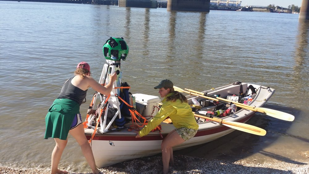 After months on the Mississippi River, OAR Northwest rowers Audra and Calli arrived in Baton Rouge. Researchers at LSU met the rowers near the new bridge to retrieve water samples the rowers had collected for analysis of microbe DNA. Photo by Dawn Jenkins.