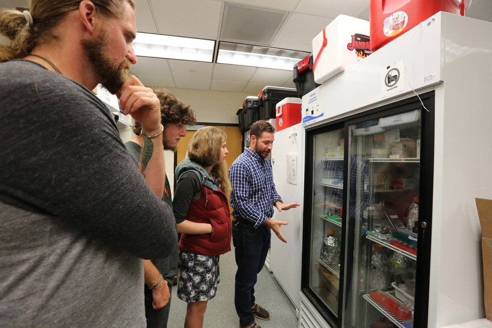 Cameron Thrash shows the OAR Northwest crew around his microbiology lab.