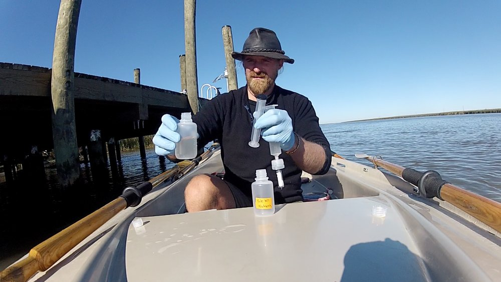 "What science looks like at LSU. OAR Northwest rowers have been collecting water samples for analysis of microbes living in the Mississippi River. LSU microbiologists conduct tests on the water samples, for example extracting DNA. In this image, OAR Northwest founder Jordan Hanssen samples water from the river for the Thrash lab. ""We use their DNA to figure out who they [the microbes] are and what they do."" - Dr. Cameron Thrash."