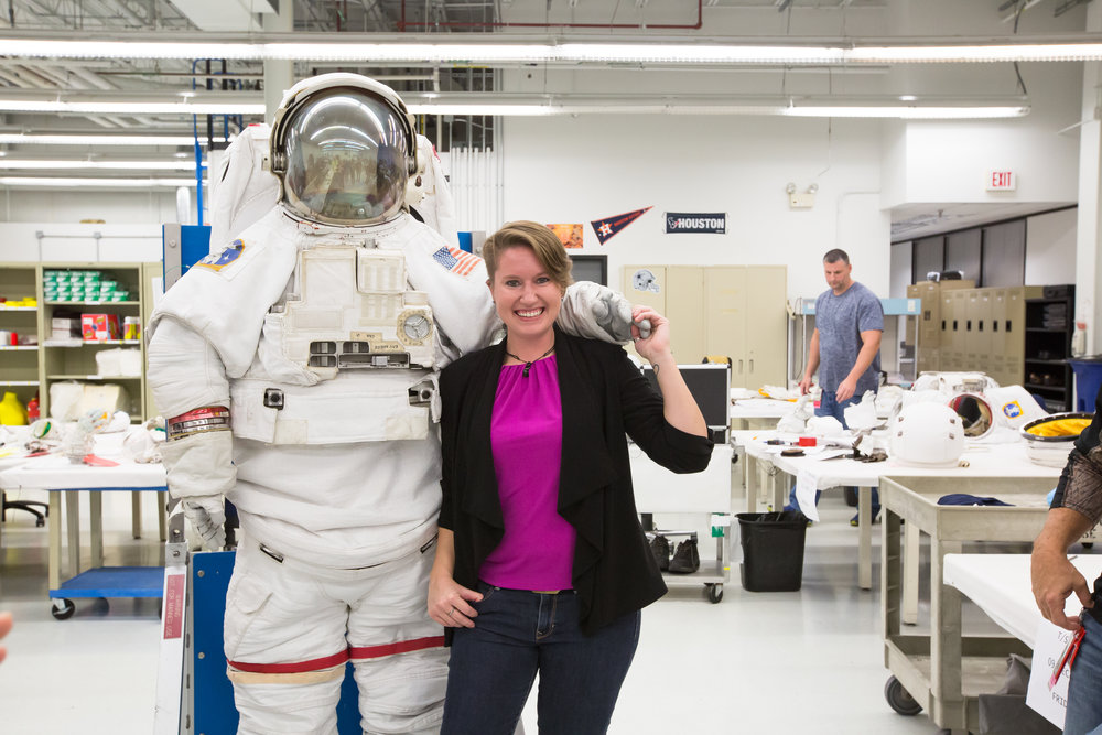 Nicki Button with a spacesuit in the suit lab of NASA's Neutral Buoyancy Lab! Photo by Paige Jarreau.