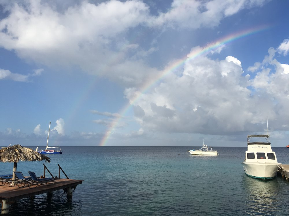 """A rainbow is a good omen for a dive day.  Here you can see it over the top of the dive boat I was going out on that day in Bonaire."" - Alicia Reigel"