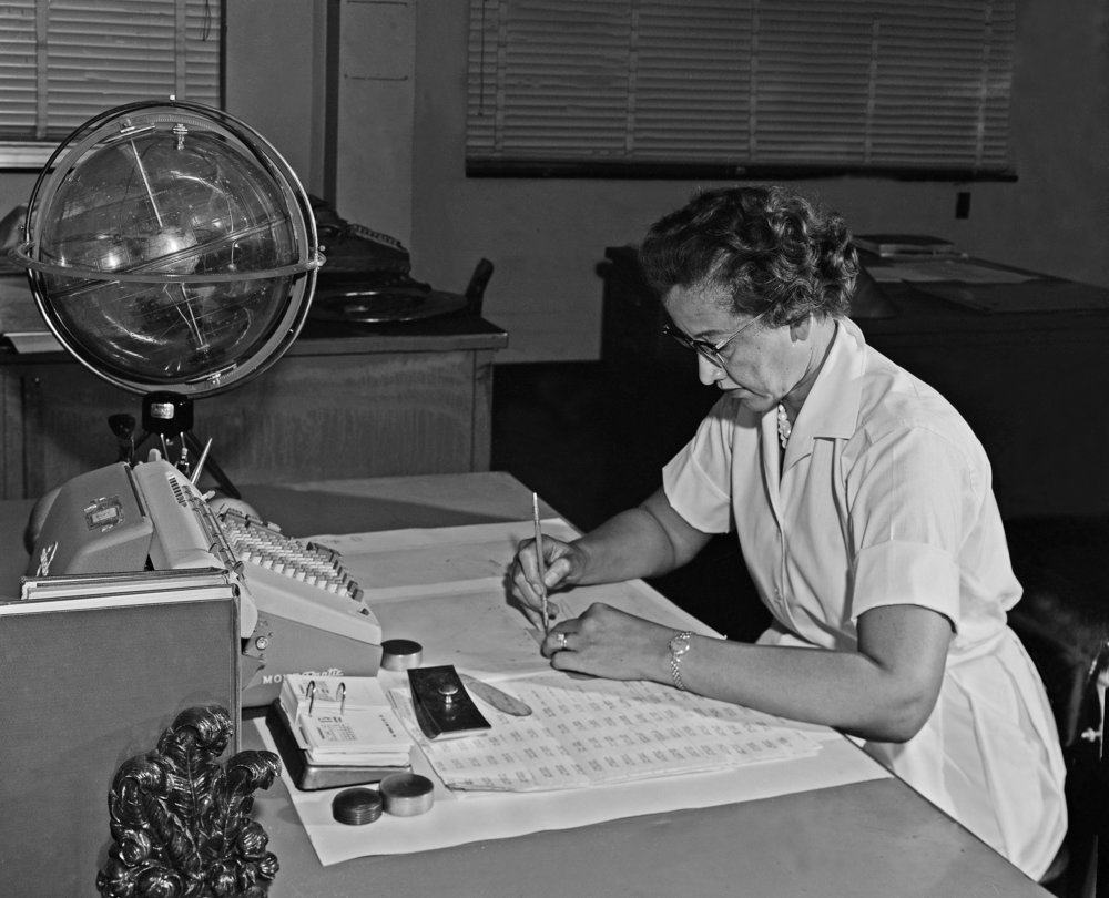 "Katherine Johnson sits at her desk with a globe, or ""Celestial Training Device."" Credits: NASA."