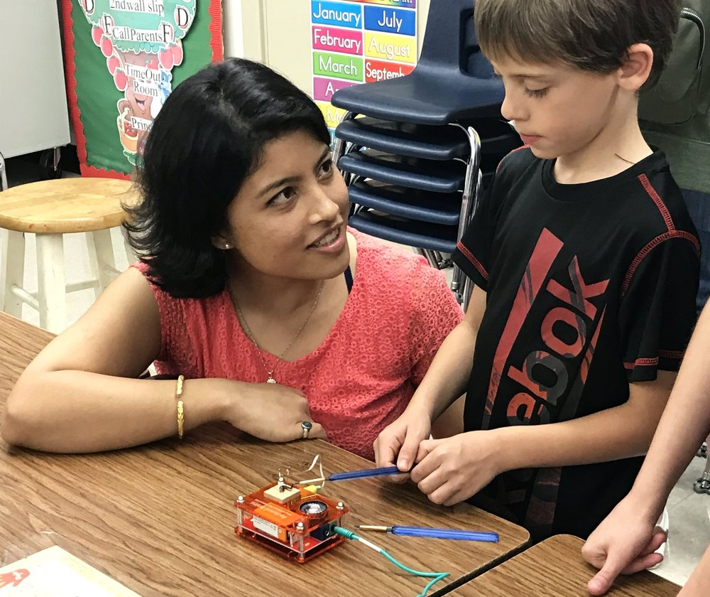 LSU neuroscience researcher and graduate student Sonu Shrestha Baral shows an elementary school student how to activate the neurons in a cockroach leg. Photo by Julie Butler.
