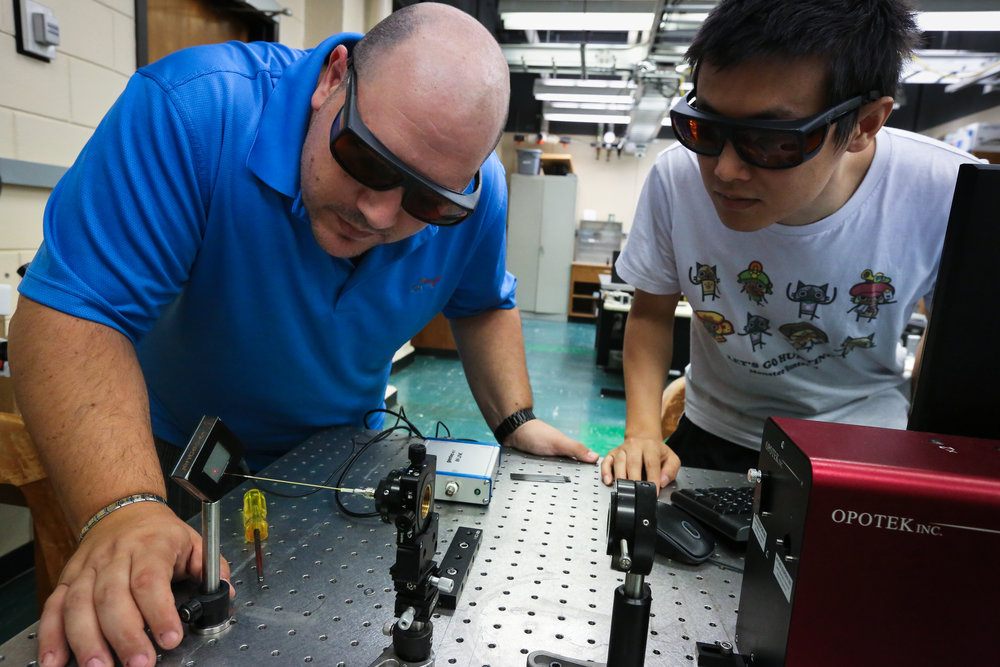 Image: LSU researchers Fabrizio Donnarumma and Fan Cao set up an infrared laser system used to remove fingermark materials from a surface for chemical analysis. Photo by Paige Jarreau.